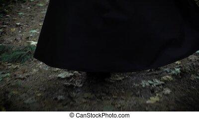 A woman in a long black cloak with a hood is walking along...