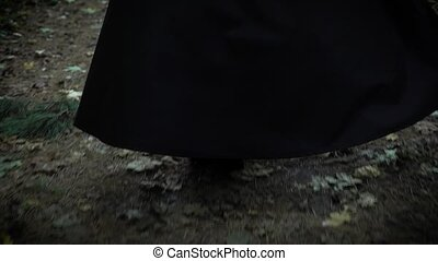 A woman in a long black cloak with a hood is walking along...