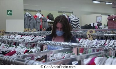 woman in a mask chooses clothes in a store