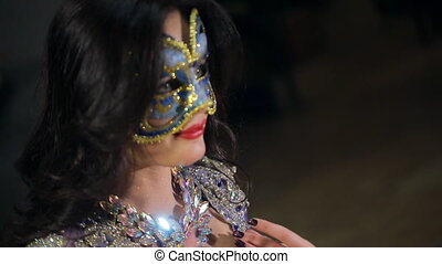 A woman in a mask with an open neckline makes a motion with...