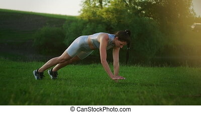 a woman in a Park on the grass stands in the plank exercise and raises her right and left hand in turn. static exercise on abs. High quality 4k footage