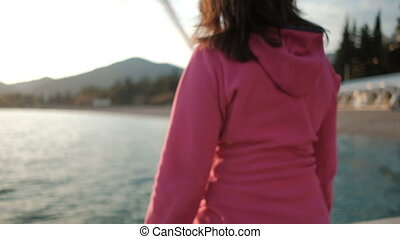 A woman in a pink jacket is sitting at the sunset by the lake.
