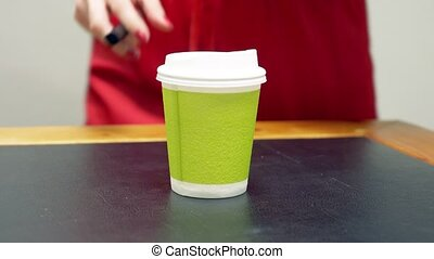 A woman in a red dress takes a cardboard cup of coffee and...