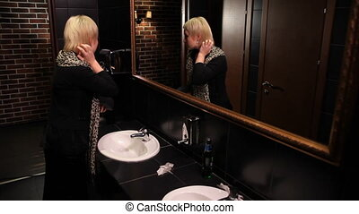 A woman in a restroom in the mirror admiring