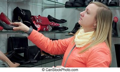 A woman in a shoe store chooses shoes. Close-up