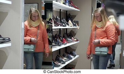 A woman in a shoe store chooses shoes.
