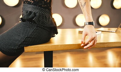 A woman in a skirt sits at an office desk.