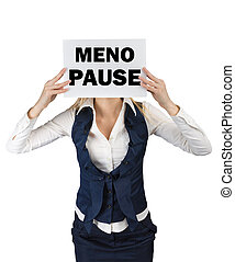 A woman in a suit standing holding a piece of paper with the word menopause at the level of the face