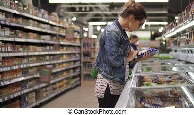 A woman in a supermarket, choosing frozen vegetables from the refrigerator