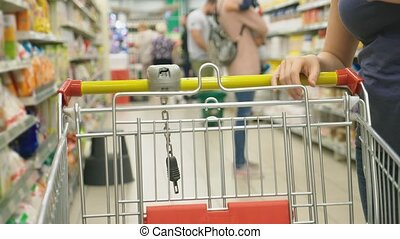 A woman in a supermarket is passing by the basket past the...