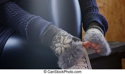 A woman in a warm sweater and gloves enshrines white skates....