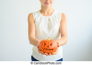 A woman in a white blouse holds a pumpkin for Halloween. Close-up of female hands with a lantern jack on a white background on the eve of All Saints. foreground. Trick or treat. Scary grimace.
