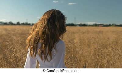 A woman in a white dress is walking along a field with wheat.