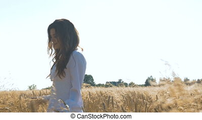 A woman in a white dress is walking along a field with wheat. Slow motion,