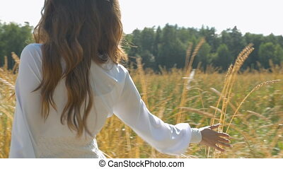 A woman in a white dress is walking along a field with wheat. Slow motion