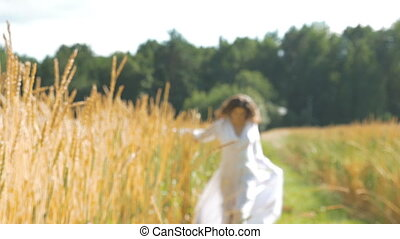 A woman in a white dress is walking along a field with wheat. Slow motion, out of focus