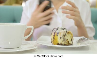 A woman in a white shirt uses her smartphone and eats with a...