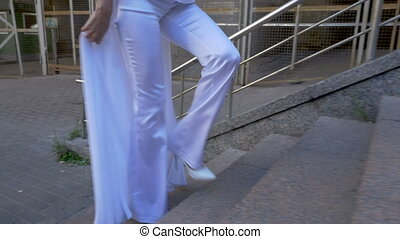 A woman in a white suit climbs the stairs.