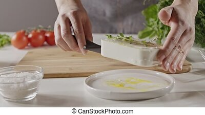 A woman in an apron puts a piece of soft cheese on a wooden...