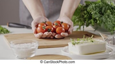 A woman in apron holds a handful of red cherry tomatoes in...
