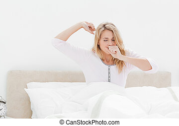 A woman in bed, leaning upright one arm stretching out and one hand covering her mouth as she yawns.