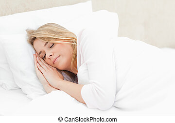 A woman in bed with her hands and head both on the pillow as she sleeps.