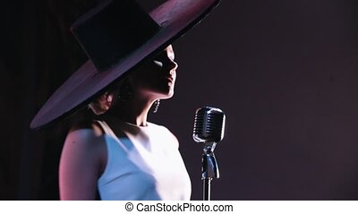 A woman in big black elegant hat stands by the mic and...