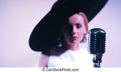 A woman in big black elegant hat walks to the mic and starts singing. Close up