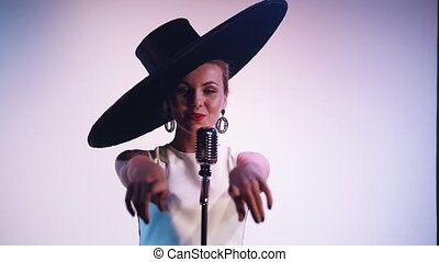 A woman in big retro hat flirty singing on the stage on...
