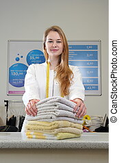 Woman in dry cleaning with Towels on counter