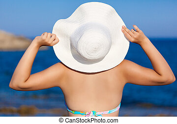 A woman in hat is posing