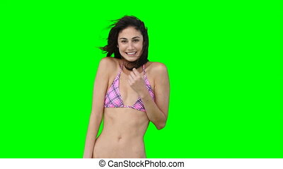 A woman in her bikini dances while smiling