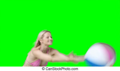 A woman in her bikini passes a beachball back and forth