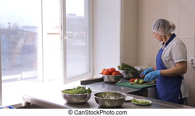A woman in kitchen in an apron spread sliced tomatoes and...