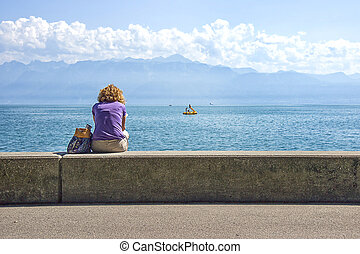A woman in Lausanne quay of Geneva Lake in summertime