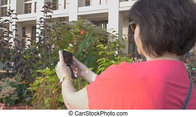 A woman in red clothes takes pictures of flowers on her mobile phone.