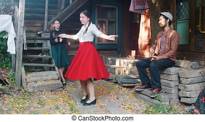 A woman in red skirt dancing by the music - a man playing...