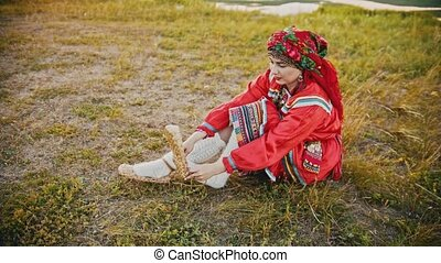 A woman in russian folk clothes putting on bast shoes -...