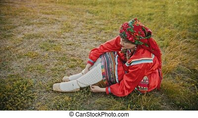 A woman in russian red folk clothes putting on bast shoes -...