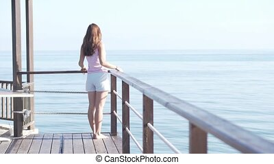 A woman in short shorts stands on the edge of a wooden bridge