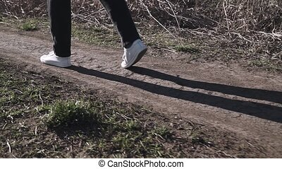 A woman in sports shoes walks along a rough forest road.