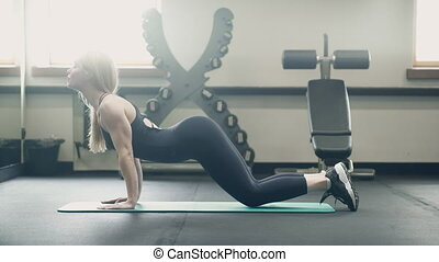 A woman in the gym makes stretching exercises for her back muscles.