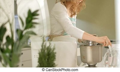 A woman in the kitchen prepares bread in a bread maker