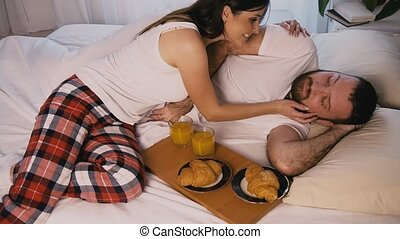a woman in the morning in the bedroom woke her husband breakfast in bed