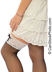 A woman in white dress and fishnet stockings