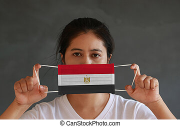 A woman in white shirt with Egypt flag on hygienic mask in her hand and lifted up the front face on dark grey background. Tiny Particle or virus corona or Covid 19 protection.