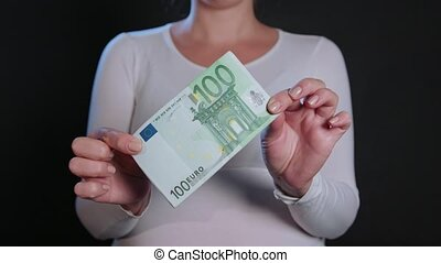 A Woman in White Sweater Holding Cash - A woman in a white...