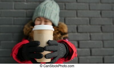 A woman in winter clothes drinks hot tea or coffee from a gray brick wall background. Slow motion.