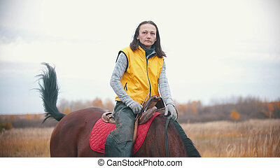 A woman in yellow jacket on a horse back and looking into the distance