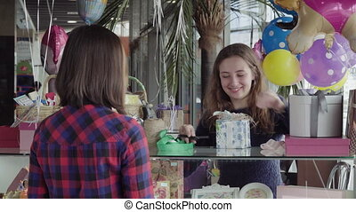 A woman is buying a holiday gift - Young woman gift seller...